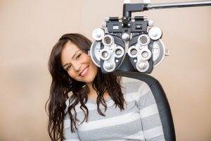 woman with vision insurance sitting next to a phoropter